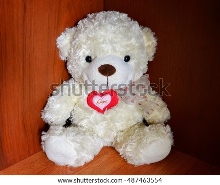 White teddy bear in vintage wooden box.