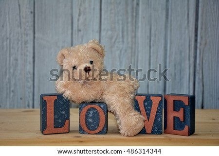 White teddy bear is on cube with the word love in front of white wooden wall