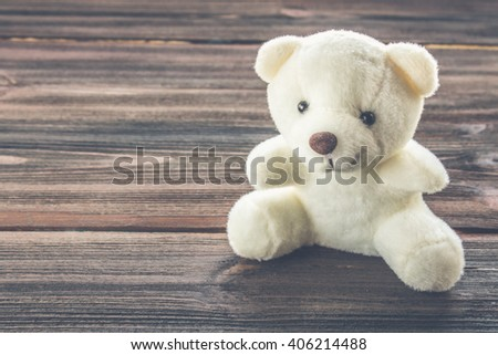 White teddy bear on a wooden background. - stock photo