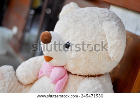 White teddy bear tied with pink scarf. - stock photo