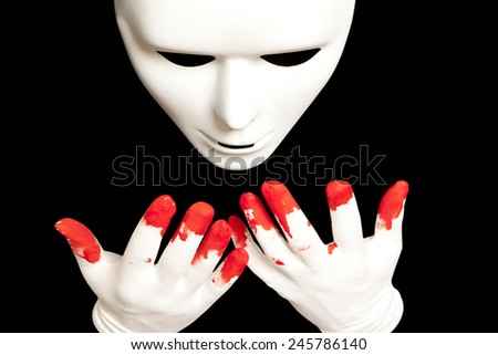 White theatrical mask and blood on their hands - stock photo