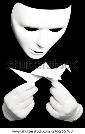 White theatrical mask and paper japanese crane isolated on black - stock photo
