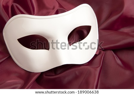 White theatrical mask and silk fabric  - stock photo