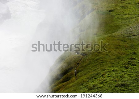 White thick steam and bright green hill covered with fresh moss, Gulfoss waterfall, Iceland - stock photo