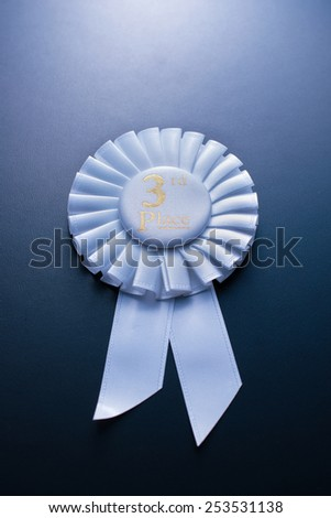 White third place winner of the socket with a pleated ribbon on a dark background - stock photo