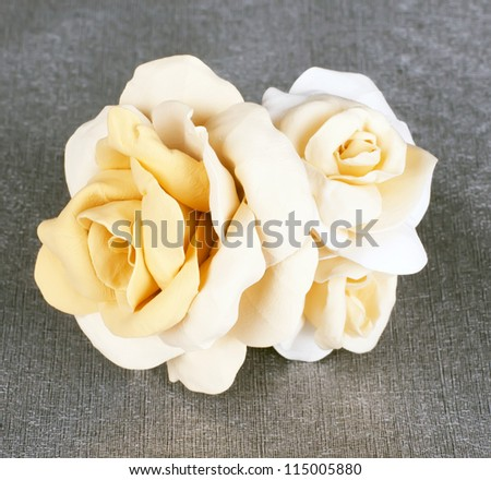 white three rose in the wedding crown with gold the centers fresh from a cold porcelain on the grey fabrics pearl tint - stock photo
