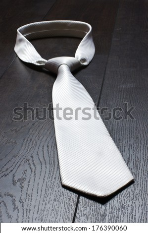 White tie on the wooden floor - stock photo