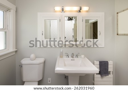 White tiled modern bathroom interior with rectangle sink and mirror. - stock photo