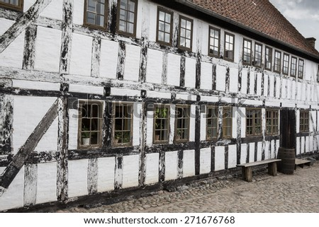 White timbered house, with  a bench and rainbarrel in the old town Den Gamle By in Aarhus Denmark