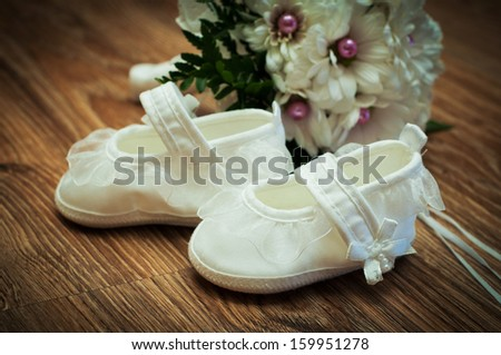White tiny shoes and white bouquet on a wooden floor - stock photo