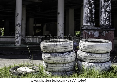 White tires, stack 2 stack 3 line behind an abandoned building