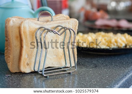 White toast in a rack with scrambled egg in the distance
