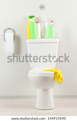 White toilet bowl and  cleaning supplies in a bathroom - stock photo