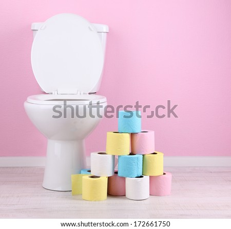 White toilet bowl and colorful rolls of toilet paper, in  bathroom - stock photo