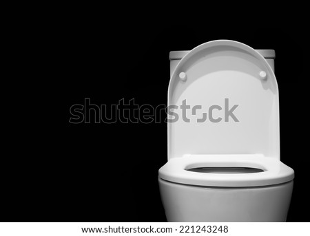 White toilet bowl in a bathroom with black background - stock photo
