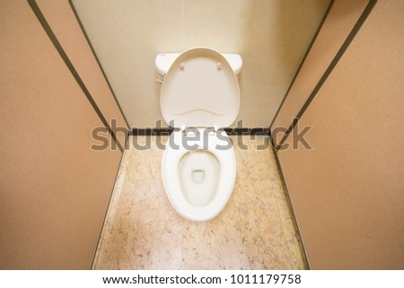 White toilet bowl in the public restroom.