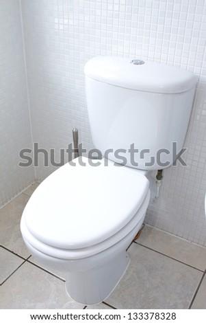 white toilet in a clean white tiled bathroom - stock photo