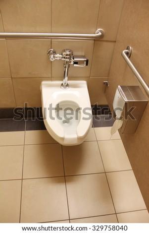 White toilet with handicap cars around it - stock photo