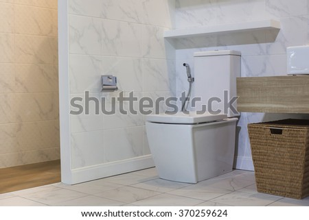 white toilet with wooden and white tile theme - stock photo