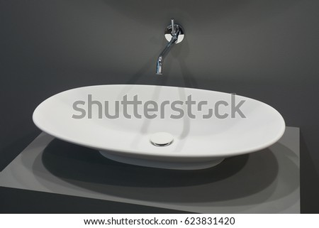White top ceramic washbasin, glossy metal mixer on gray background