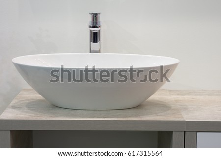 White top ceramic washbasin with glossy metal mixer
