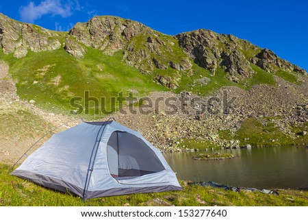 white touristic tent on a mountain lake coast - stock photo