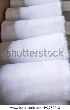 white towel on a shelf in the closet
