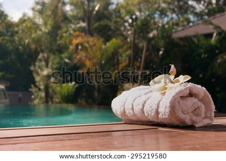 White towel on the edge of the pool against the backdrop of palm trees - stock photo