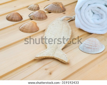White towel, seashells and fish shaped wisp on the wooden planks