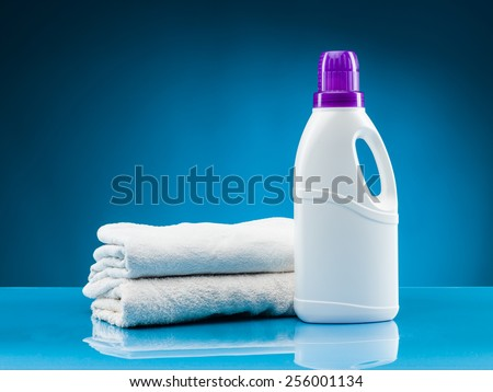 white towels and liquid laundry detergent against blue background - stock photo