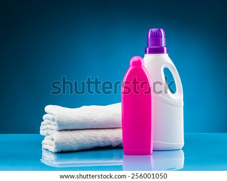 white towels, liquid laundry detergent and softener against blue background - stock photo
