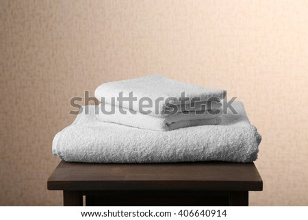 White towels on brown chair over beige background - stock photo