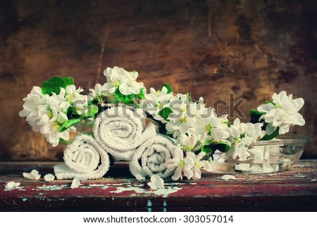 White Towels put in Rolls with Branch of the Apple Blossoms. Composition in Vintahe Style for Decoration SPA Salon. Toned image - stock photo