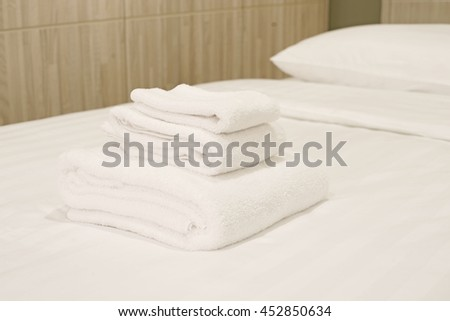 white towels rolled and piled on bed