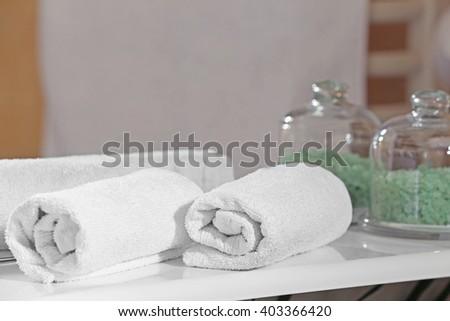 White towels with green salt on a shelf in bathroom - stock photo