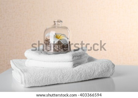 White towels with salt and tropical flower on table over beige background - stock photo
