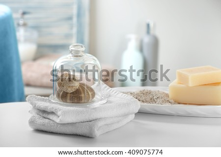 White towels with shells on bathroom table - stock photo