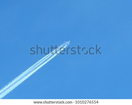 White trace of passenger plane across the blue sky. Jet airplane is flying high