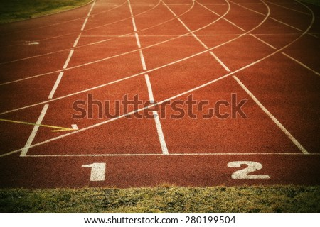 White track number on red rubber racetrack, texture of running racetracks in small stadium