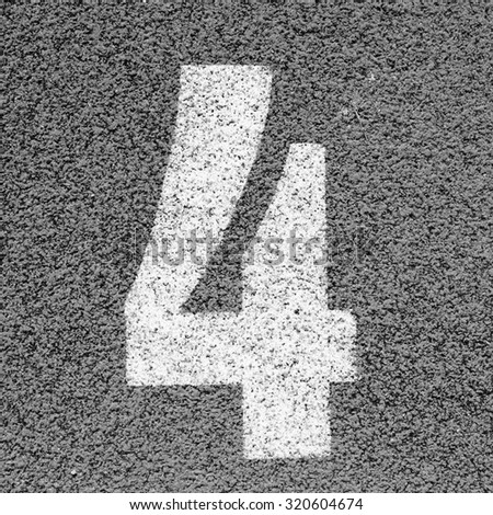 White track number on rubber racetrack, texture of running racetracks in small stadium.  Black and white photo