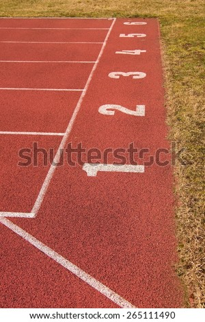 White track number on sprint start. The red rubber racetrack small stadium, texture of running racetracks. - stock photo