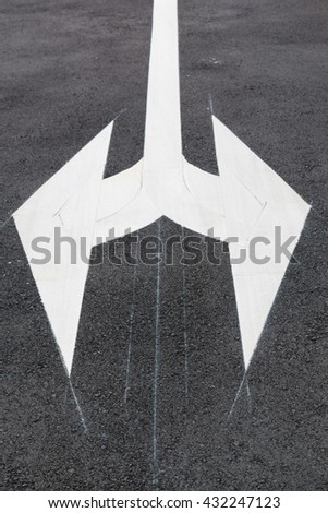 White traffic arrow signage on an asphalt road