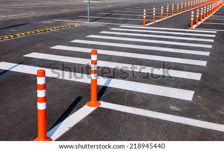 White traffic markings with a pedestrian crossing on a gray asphalt parking lot - stock photo