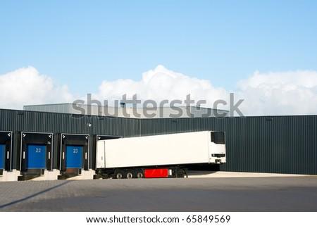 White trailer in front of loading docks. - stock photo