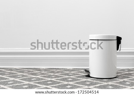 White trash can, with copy space on the wall. - stock photo