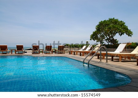 White trestle-beds near the resort's pool - stock photo