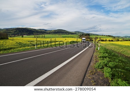 White truck arrives from a distance on an asphalt road between the yellow flowering rapeseed field in the rural landscape. Wooded mountains in the background. Blue sky with white clouds. - stock photo