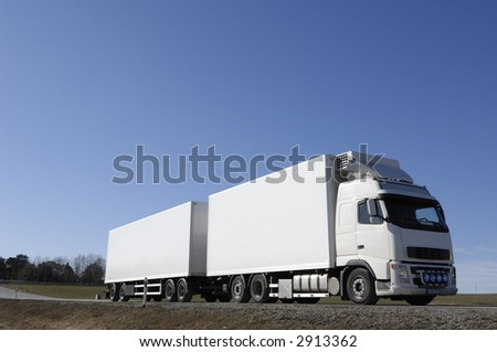 white truck driving on country-road under blue sky - stock photo