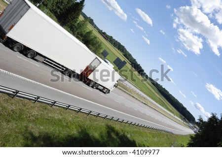 white truck driving on highway surrounded by country-side and in an extreme angle of view - stock photo