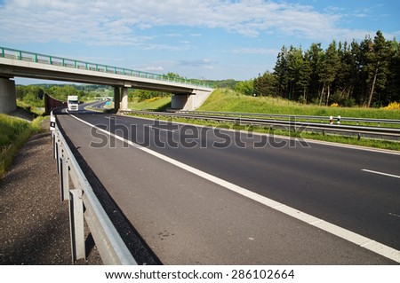 White truck entering under a concrete bridge over a highway in a wooded landscape. Noise protection wall. White clouds in the blue sky. - stock photo